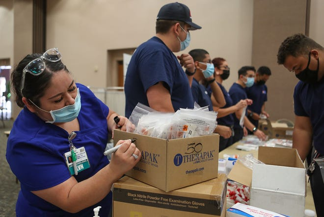 Griselda Aguilar, a licensed vocational nurse, helps prepare Covid-19 testing kits for the free testing at the Palm Springs Convention Center.  The testing was being done through the Riverside University Health System, October 13, 2020.