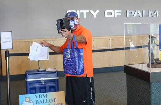 Palm Springs resident Henry Chinchilla takes a selfie as he drops his Vote by Mail ballot off at Palm Springs City Hall, October 13, 2020.