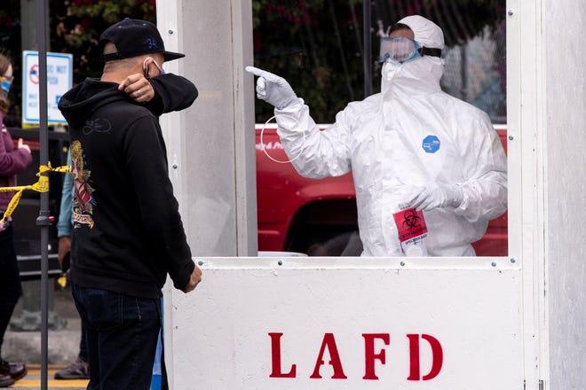 Un bombero le pide a un hombre que tosa antes de entregarle un hisopo para que tome una muestra en su boca en un sitio de prueba emergente Covid-19 para personas sin hogar en medio de la pandemia de coronavirus en Skid Row, Los Ángeles, California, EE. UU., 20 Abril de 2020.