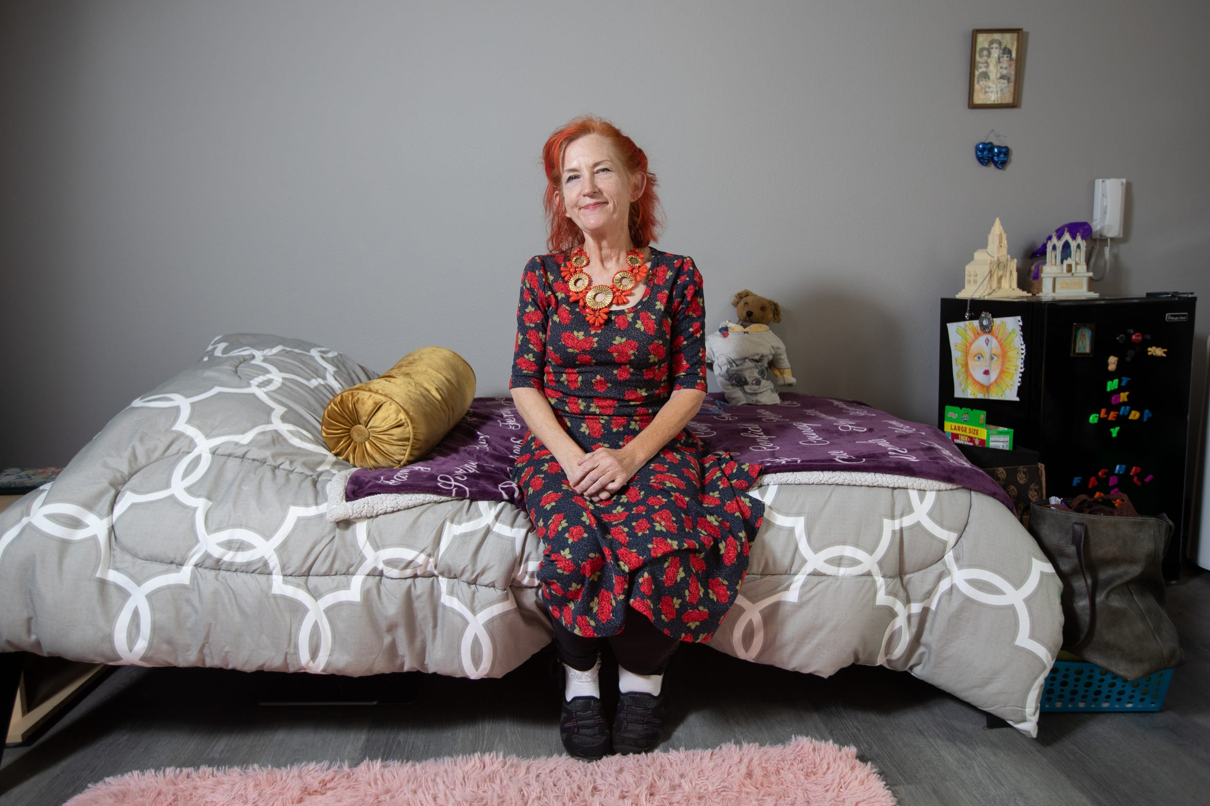 Glenda Meyer, 57, sits on the bed of her apartment at Redwood Crossings.