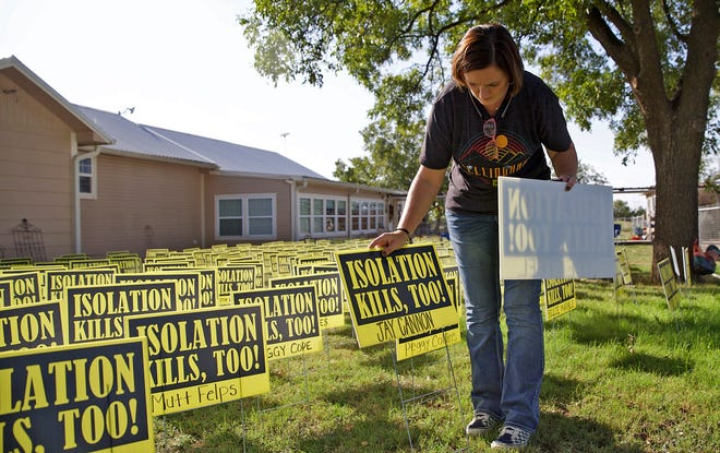 Amanda Horner places signs in her yard Tuesday, Oct. 13, 2020 with the names of 300 people who are in isolation in nursing homes and state supported living centers in Texas due to COVID-19 restrictions.