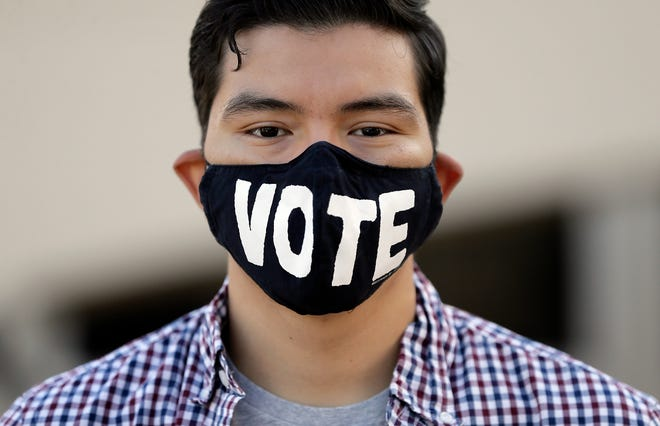 "Diego Reyes wears a ""Vote"" mask as he waits in a long line to vote early at the UTEP Student Union Tuesday, October, 13, 2020."