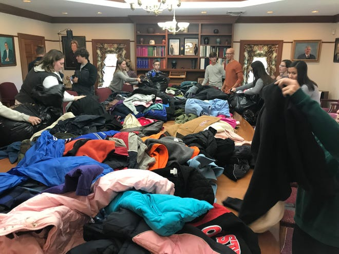 Volunteers sort clothes during a previous winter clothing drive by the Muskingum County Community Youth Foundation.