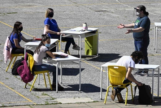 High school students in their last year, attend classes at an improvised classroom in the yard of their school in Buenos Aires, Argentina, on Oct. 13, 2020 amid the virus lockdown against the spread of the novel coronavirus, COVID-19 pandemic. The city government partially allowed students on their last year to attend face-to-face classes under a strict sanitary protocol and in the school open spaces.
