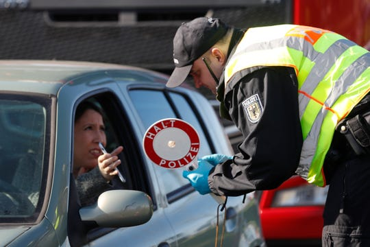 A German police officer checks authorization for a woman to enter Germany at the German-France border in Kehl, Germany, on March 16, 2020. European Union countries are set to adopt a common traffic light system to coordinate traveling across the 27-nation bloc, but a return to full freedom of movement in the midst of the COVID-19 pandemic remains far from reach.