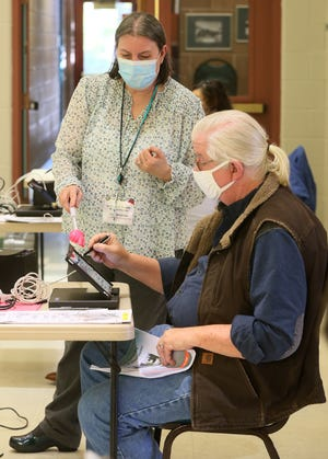 Summit County Board of Elections worker Pam Wenhardt uses a pointer as she helps Keith Rutherford during poll worker training at the Ellet Community Center on Tuesday in Akron. Rutherford and his wife, Cheryl, attended the training. Summit County is still accepting poll worker applications.