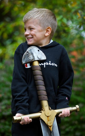 Everett Walker, 8, tries his hardest to pull the sword made by Michael Marras out of the stump at West Exchange Street and Elmdale Avenue on Wednesday.