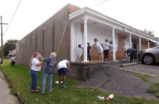 Volunteers apply white primer paint Sept. 12 to the front and side of the former Hometown Carpet & Flooring store at 1006 S. Arch. The building will be the site of a Habitat for Humanity ReStore and the Alliance Area Habitat agency's headquarters.