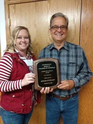 Valerie Spreng, executive director of the Loudonville Chamber of Commerce, presents on Wednesday the Loudonville Chamber of Commerce Community Service Award to Roger Stitzlein, retired CEO and general manager of the Loudonville Farmers Equity.