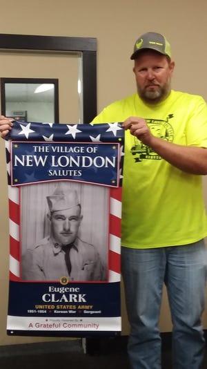 Inspire New London member Clint Cherry holds a banner honoring Eugene Clark.