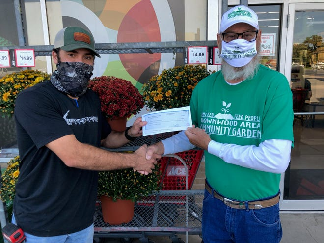 Weston Jacobs, owner of Weakley Watson's Ace Hardware Store, presents Carl Boivin, president of the Brownwood Area Community Garden, with a check for $700.39 from Weakley Watson's Roundup program. [Photo contributed]
