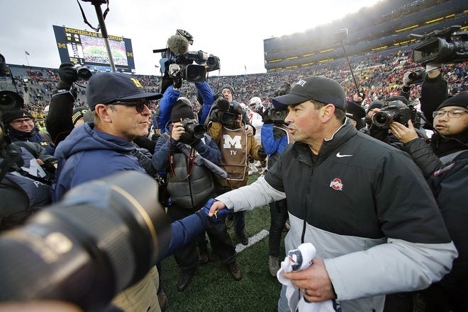 Ohio State Buckeyes head coach Ryan Day shakes the hand of Michigan Wolverines head coach Jim Harbaugh after the Buckeyes won 56-27 during their game at Michigan Stadium in Ann Arbor, Michigan on November 30, 2019. [Kyle Robertson/Dispatch]