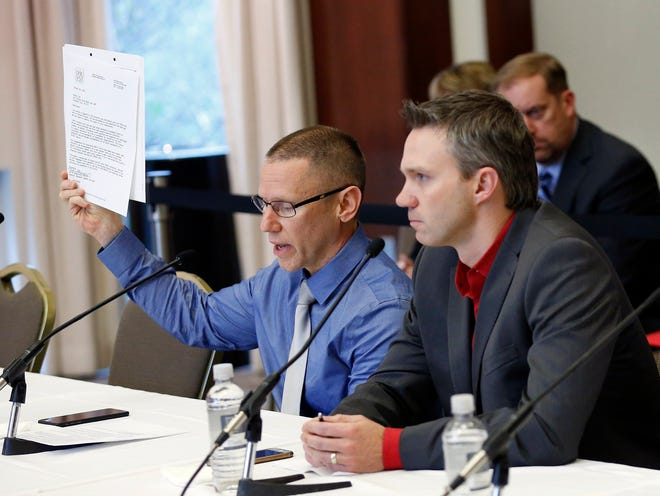 In this file photo, victims of Dr. Richard Strauss, Brian Garrett, right, listens as Stephen Snyder Hill holds a document from Student Health Services while testifying to the extent of their abuse during an Ohio State University Board of Trustees meeting at the Longaberger Alumni House on Nov. 16, 2018. Some of the former students returned to address the board for the third time on Thursday.