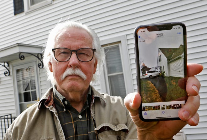 Ralph Walker holds up his phone Wednesday to show a photo of a car that crashed into his home on East Livingston Avenue on Jan. 1. Livingston has a high rate of speeders and crashes compared to many other parts of Columbus, police said. [Eric Albrecht/Dispatch]