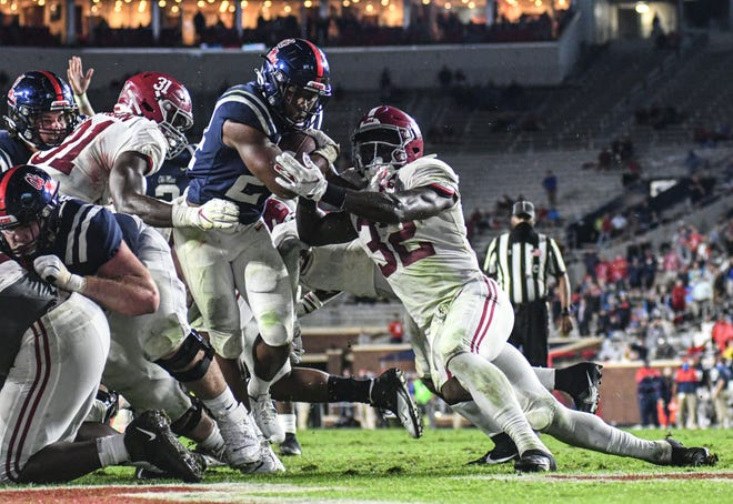 Mississippi running back Snoop Conner steps through tackle attempts by Alabama's Will Anderson Jr. (31) and Dylan Moses (32) to score a touchdown against the Crimson Tide last Saturday. Ole Miss gained 647 yards in its 63-48 loss, the highest total against an Alabama defense.