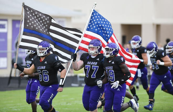 The Fletcher High School football team from Neptune Beach takes to the field with players carrying the American Flag and the Blue Lives Matter flag on Sept. 18.