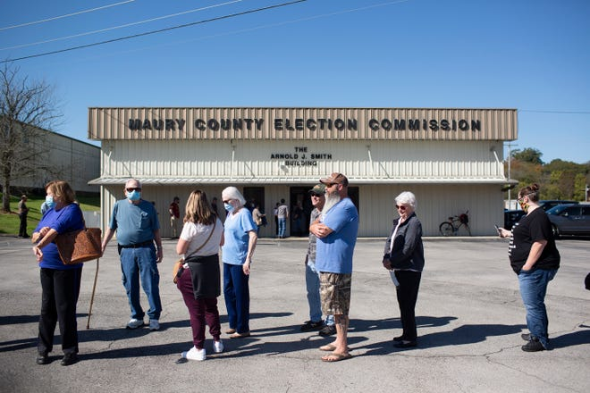 Voters wear masks and social distance as they wait in a long line to cast their ballots on the first day of early voting for the presidential, state and local elections at the Maury County Election Commission in Columbia, Tenn., on Wednesday, Oct. 14, 2020.