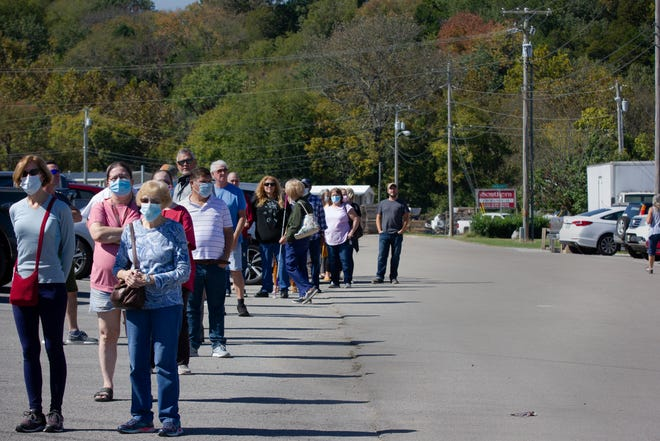 Stephanie Powers right and Shirley Whitwell ware masks as the two wait in an hour-long line to cast their ballots on the first day of early voting for the presidential, state and local elections at the Maury County Election Commission in Columbia, Tenn., on Wednesday, Oct. 14, 2020.
