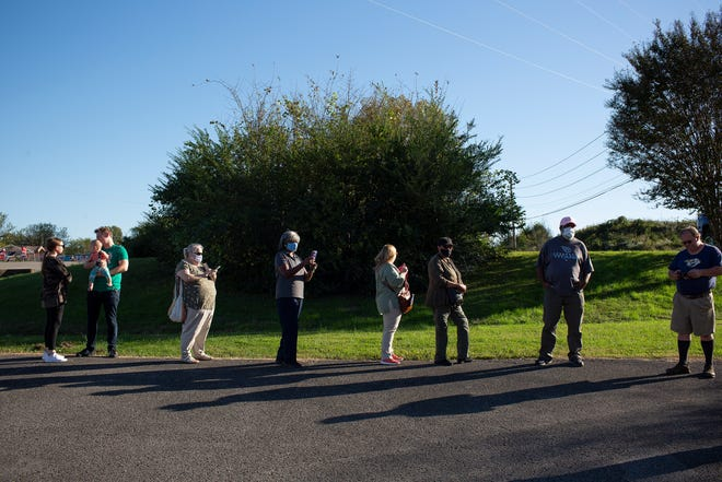 Voters who are among the last to vote for the day wear masks and social distance as they wait in a long line to cast their ballots on the first day of early voting for the presidential, state and local elections at the Maury County Election Commission in Columbia, Tenn., on Wednesday, Oct. 14, 2020.