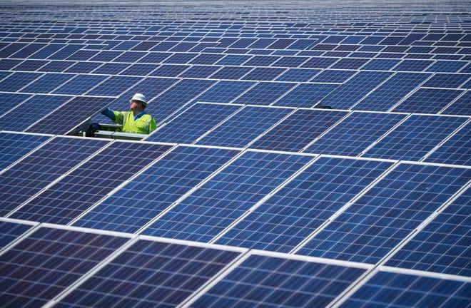 A Duke Energy employee works on solar panels.