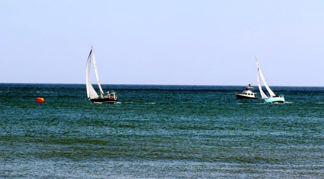 Sailboats competing in the last race of the Commodore's Cup head for a course buoy Sunday.
