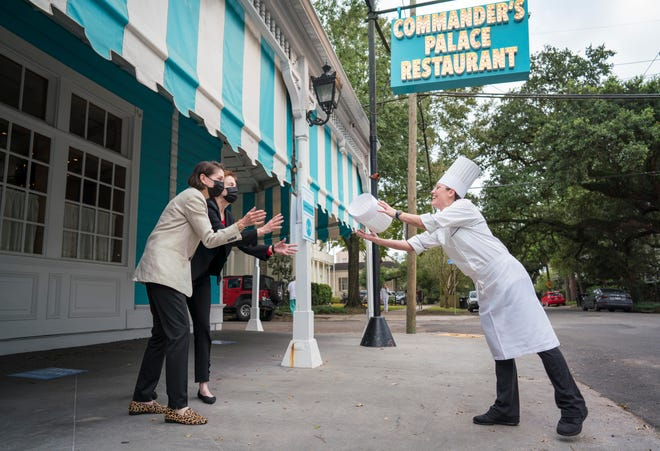 Commander's Palace proprietors Lally Brennan and Ti Martin, left, toss the chef's toque to Meg Bickford outside the restaurant in New Orleans. Bickford will be the first female executive chef in the storied history of the restaurant.