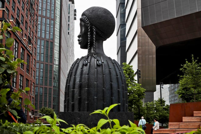 "A bronze bust of a Black woman entitled ""Brick House,"" by Chicago artist Simone Leigh, stands among buildings and vegetation in the High Line park in New York."