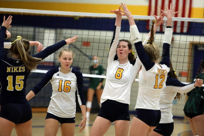 Notre Dame High School's Gabriella Deery (8) and Kathryn Stephens (16) celebrate a point with teammates during their game against West Burlington High School Tuesday, Oct. 13, at Notre Dame's Father Minett Gymnasium.