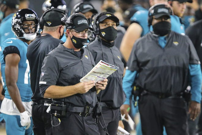 Jaguars offensive coordinator Jay Gruden, seen here with his playsheet during last month's loss to the Miami Dolphins, admits he has to be more patient as a play-caller to not abandon the running game. (AP Photo/Gary McCullough)