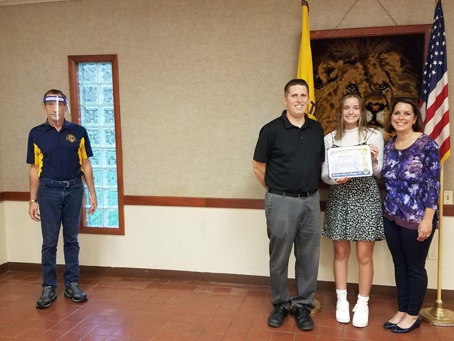 Tallmadge Lions club member Mark Salerno, left, presents the Jim & Ida VanGlider Tallmadge Lions Club October 2020 Student of the Month Award to Halle Caruso  with her parents Marc and Monica Caruso.