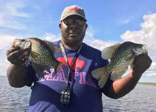 Gary Burks of Lakeland shows off a couple of specks he caught while fishing jigs in the Kissimmee River last week.