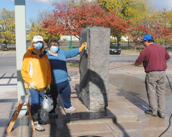 Daughters of the American Revolution members Mary Bottini, left, and Kathy Snell assist Gerard Waterman Wednesday, Oct. 15, 2020, while cleaning a monument that marks the location of Old Fort Schuyler in Utica.