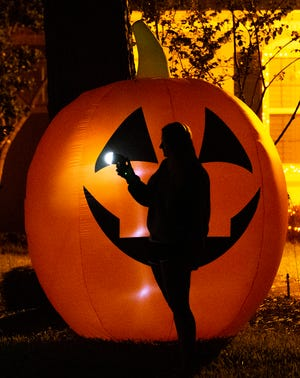 Emma Rae Horvath, 17, is silhouetted against a blow-up jack-o'-lantern outside her home in Ocala.