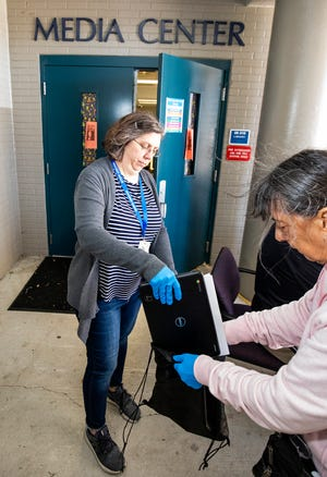 Paraprofessionals Mary White, left and Jane Farr load a Dell Google Chromebook into a bag in April for a Oakcrest student. While teachers were teaching, parents were picking up Chromebooks so that their children could learn from home while the district was shut down the last nine weeks of the 2019-20 school year.