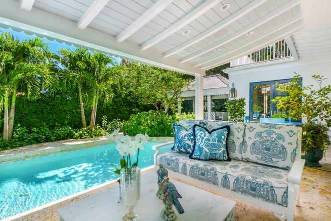 A covered patio overlooks the pool and backyard at 221 Queens Lane, a three-bedroom house listed for sale at $4.85 million on the North End of Palm Beach.