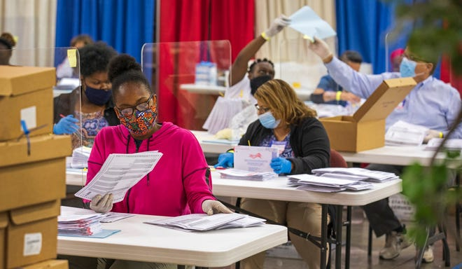 Employees with the Supervisor of Elections Office process vote-by-mail ballots Wednesday in Riviera Beach.