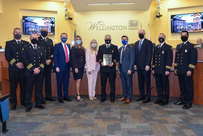 Palm Beach County Fire Rescue Capt. Craig Dube (center, holding plaque) was honored by Wellington's Village Council as the Top Firefighter for 2020 on Oct. 13.