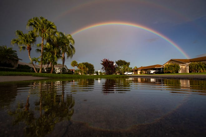 A rainbow is reflected in flooded swale along Turnstone Drive in Wellington, August 8, 2019.
