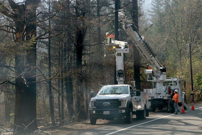 Power crews work on restoring lines along Highway 126 west of Blue River on Oct. 1.