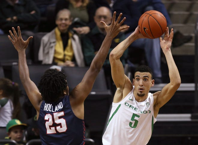 Oregon's Chris Duarte, right, looks for an open teammate under pressure from Fresno State's Anthony Holland, left, during the second half of an NCAA college basketball game in Eugene, Ore., Tuesday, Nov. 5, 2019. (AP Photo/Chris Pietsch)