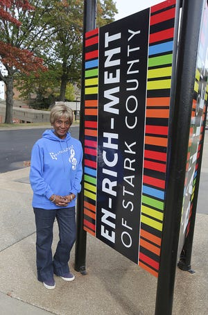 Betty Smith, executive director of EN-RICH-MENT of Stark County, stands next to a newly installed signpost at the Cultural Center for the Arts