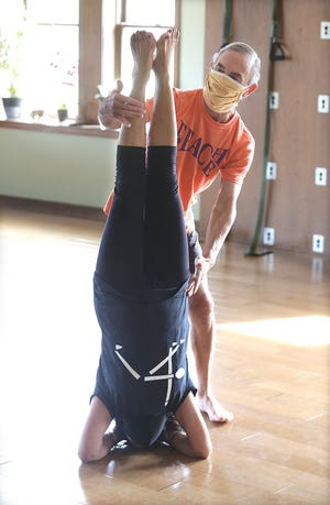 Yoga instructor Mike Curtis helps fellow instructor Shashi Gupta into a headstand pose at Yoga Central in Canton.