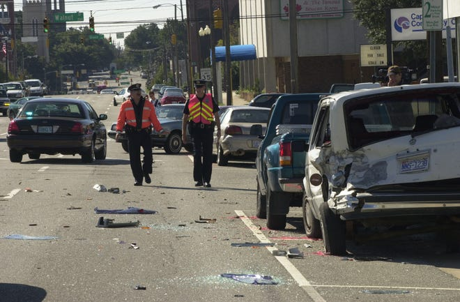Wilmington police officers weave through the debris field of glass, bumpers and other car parts following a five-car accident.