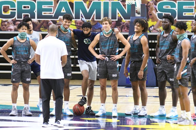 New UNCW men's basketball coach Takayo Siddle with his players during the team's first official day of practice on Oct. 14. The Seahawks open the season Nov. 25 and were picked Tuesday to finish eighth in the CAA.