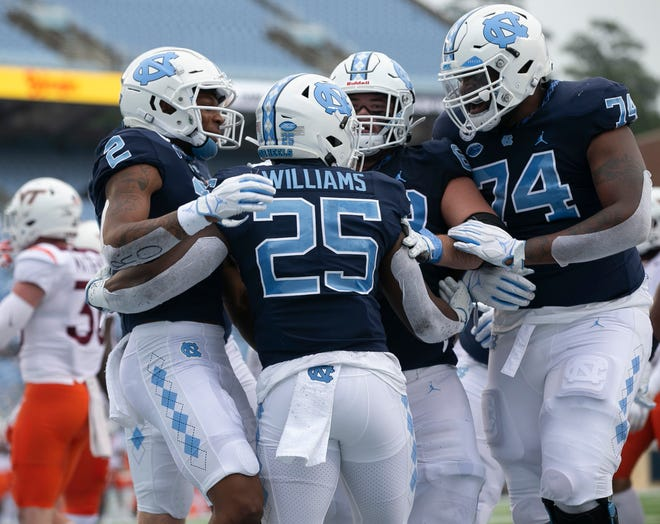North Carolina's Javonte Williams (25) celebrates with teammates after scoring on a 19-yard run for a touchdown to give the Tar Heels' a 21-0 lead on Saturday, October 10, 2020 at Kenan Stadium in Chapel Hill, N.C.