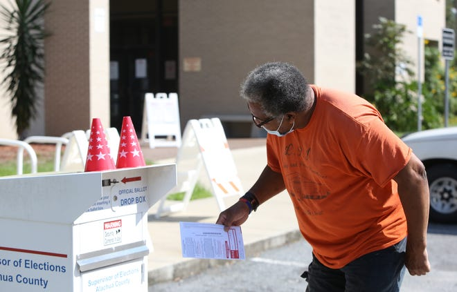 A voter puts his ballot in the drop box at the Alachua County Supervisor of Elections Office in Gainesville on Oct. 14.