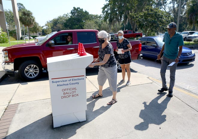 Voters wait in line to put their vote-by-mail ballots in the drop box at the Alachua County Supervisor of Elections Office in Gainesville on Oct. 14. [Brad McClenny/The Gainesville Sun]