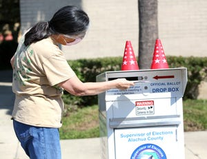 A voter puts her mail-in ballot in the drop box at the Alachua County Supervisor of Elections Office in Gainesville in 2020. The drop box will not be available until Nov. 12 for the upcoming Gainesville City Commission special election, the same day that early voting starts.