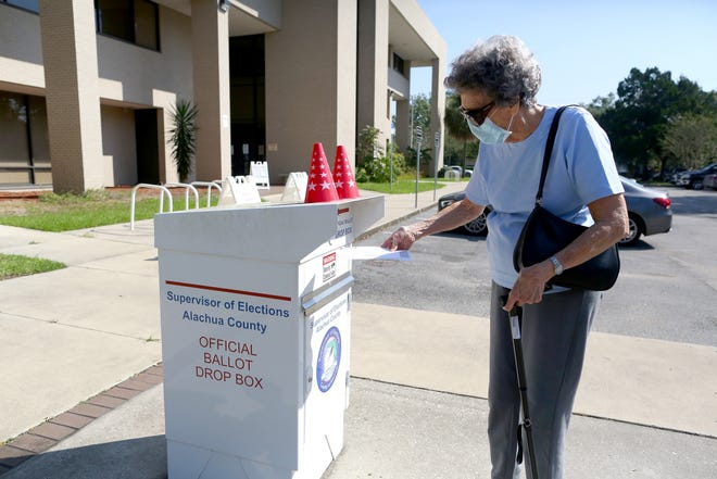 A voter puts her ballot in the drop box at the Alachua County Supervisor of Elections Office in downtown Gainesville.