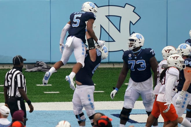 North Carolina offensive lineman Brian Anderson lifts receiver Dazz Newsome in celebration after a touchdown, as offensive lineman Marcus McKethan, right, looks on during last week's game against Virginia Tech.
